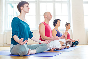 People in lotus position in a relaxation class